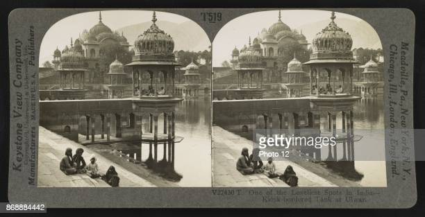 Photographic print of domed kiosks and a large cenotaph around a manmade pond with steps leading to the waters edge from walkways and plazas in Alwar...