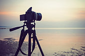 Photographing a seascape. Mirror camera on a tripod removes the dawn of the sea. A bright pink dawn.
