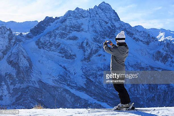 Photographing  Snow skier young woman taking landscape photo  Alps mountain