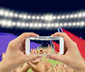 Man photographing his team's victory with a smartphone of the football stadium .The screen content is designed by me and not is copyrighted by others and created with wacom tablet and PS