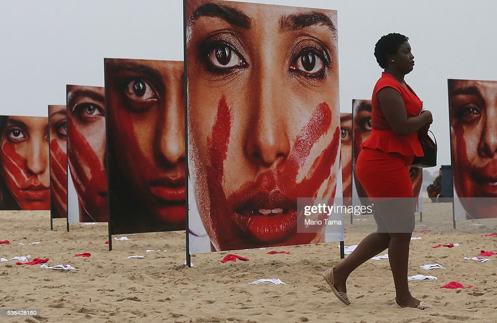 Photographs by Marcio Freitas of models portraying women who are abused are displayed on Copacabana beach with 420 pairs of underwear at a...