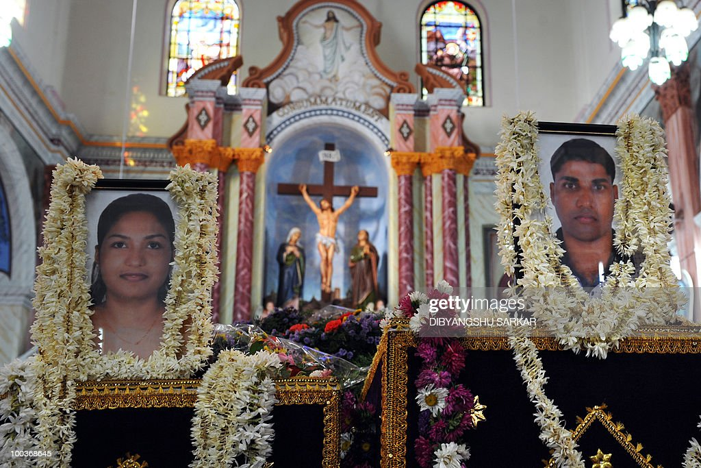 Photographs of Air India Express crash victims Naveen Walton Fernandes (R), 36, and his wife Savitha Philomene D'Souza, 24, are seen over their coffins during a funeral service at the Holy Cross Church in Mangalore on May 24, 2010. Investigators on May 22 widened the search for the 'black box' data recorder of an Air India Express that crashed into a gorge killing 158 people, as the airline denied lax safety claims. AFP PHOTO/Dibyangshu SARKAR