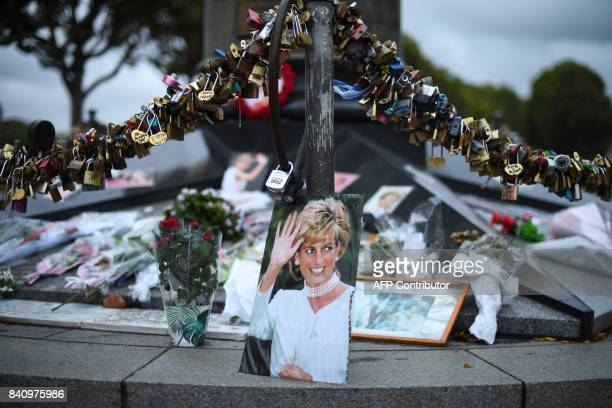 TOPSHOT Photographs of Diana Princess of Wales are seen on August 30 2017 with locks and floral tributes left over the Alma bridge in Paris to mark...