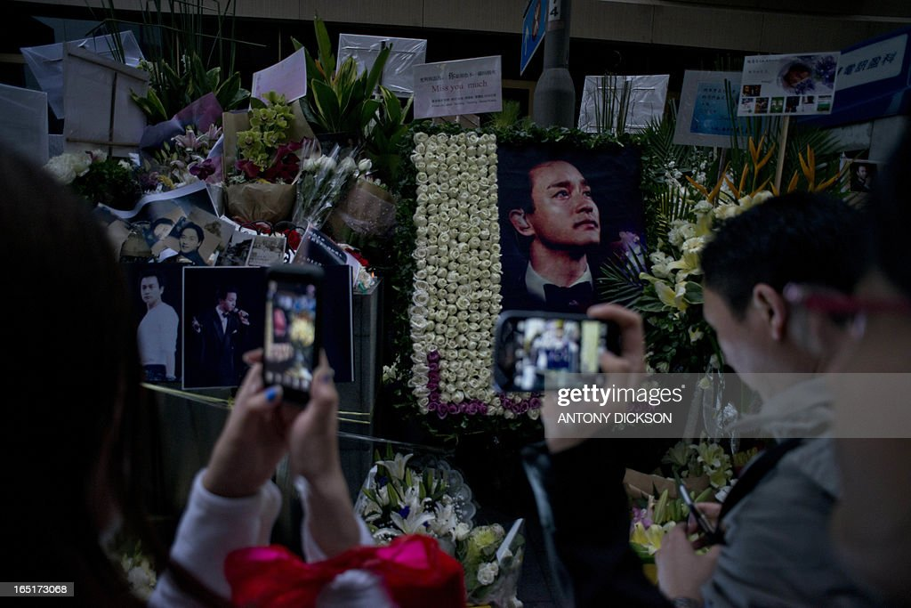 Photographs of the late Leslie Cheung Kwok-wing and flowers are displayed next to the Mandarin Oriental Hotel, during a remembrance on the 10th anniversary of his death, in Hong Kong on April 1, 2013. Cheung, a renowned singer and actor, threw himself to his death on April 1, 2003 from the hotel. AFP PHOTO / Antony DICKSON