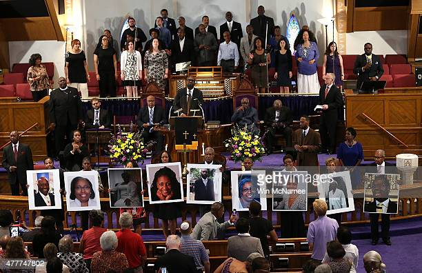 Photographs of the nine victims killed at the Emanuel African Methodist Episcopal Church in Charleston South Carolina are held up by congregants...