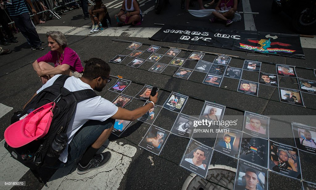 Photographs of the victims of the Orlando Pulse nightclub shooting are laid out prior to the start of the 46th annual Gay Pride march June 26, 2016 in New York. New York kicked off June 26 what organizers hope will be the city's largest ever Gay Pride march, honoring the 49 people killed in the Orlando nightclub massacre and celebrate tolerance. / AFP / the 46th / Bryan R. Smith
