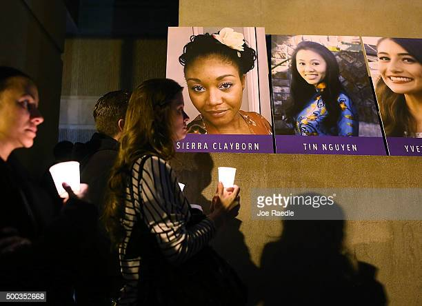 Photographs of victims of the terrorist attack on the Inland Regional Center are seen as people hold candles while attending a vigil held at the San...