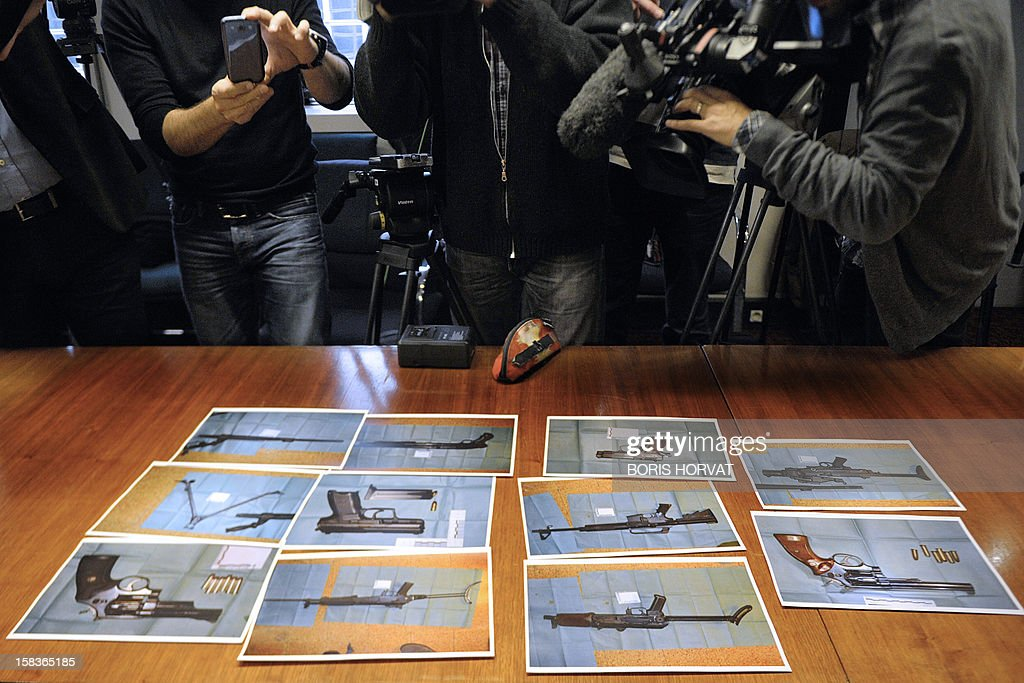 Photographs of weapons seized on the eve by French Police, are displayed to journalists on December 14, 2012, in Marseille, southern France, during a press conference held by Marseille's Prosecutor of the Republic about criminal cases occurred in Marseille in recent days, on December 14, 2012. AFP PHOTO / BORIS HORVAT