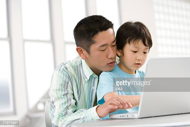 Photography of a father and son using computer, Low Angle View