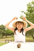 Photography of a girl playing with pine cones, Front View