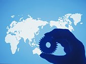 Photography of world map and a hand holding a gearwheel, Toned Image