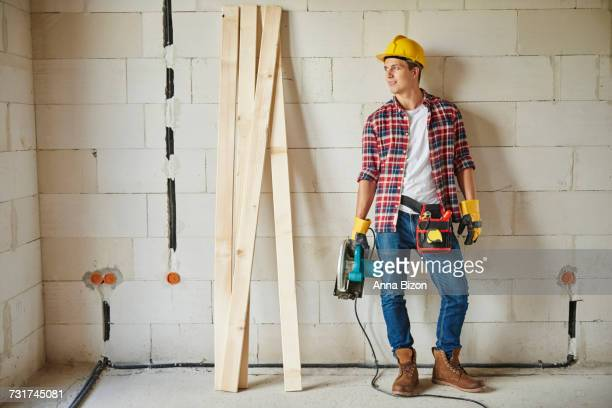 Photography of young carpenter holding jigsaw. Debica, Poland