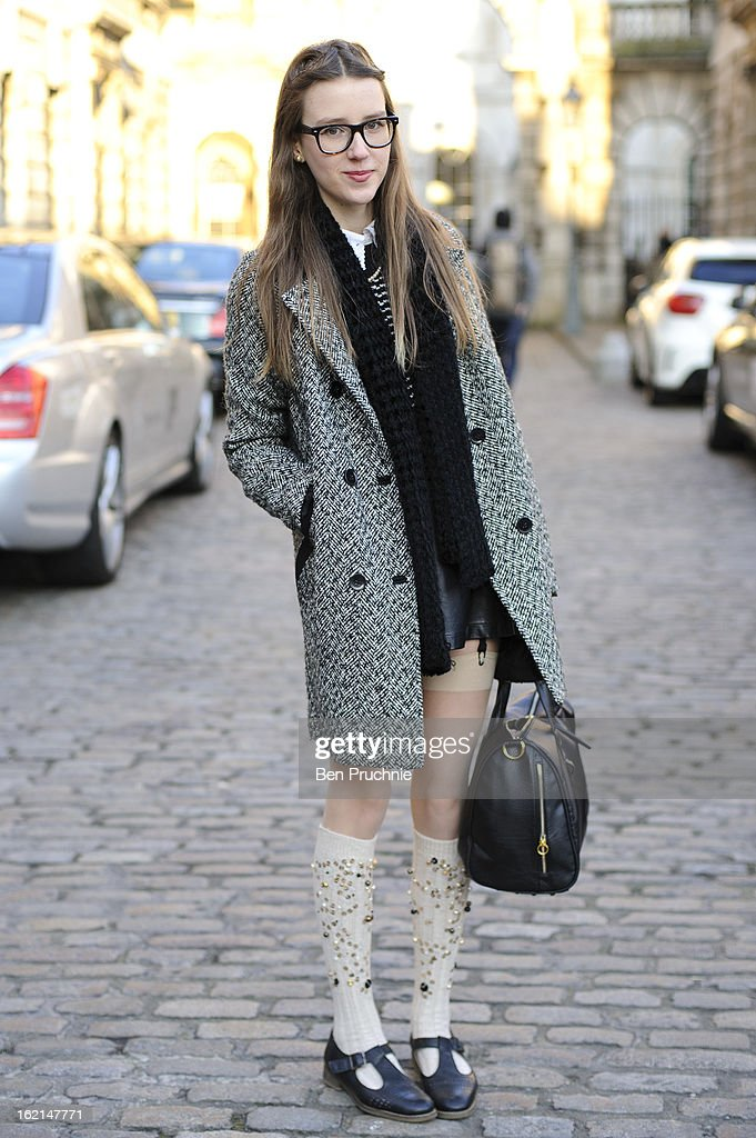 Photography student Liberty Dye poses wearing a Topshop coat and shoes with and Urban Outfitters jumper, leather skirt, Miu Miu inspired homemade socks with Anglo American glasses and gifted bag at Somerset House during London Fashion Week on February 19, 2013 in London, England.