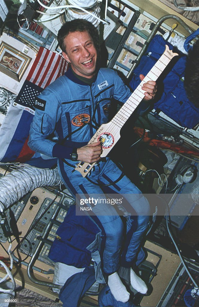 In Mir's core module the European Space Agency's Thomas Reiter tests a collapsible guitar which was a gift for the Mir from the STS74 crew in March...