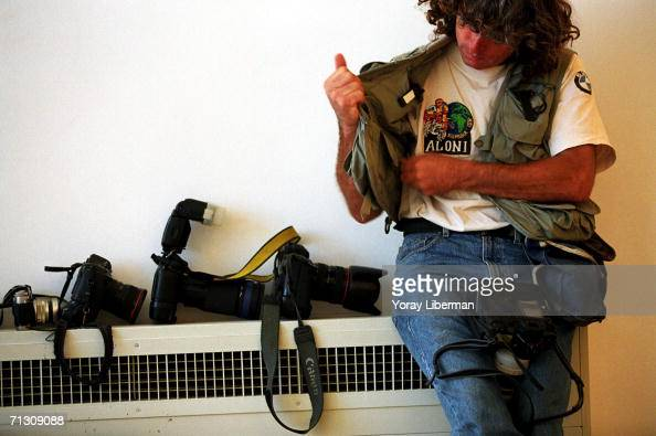 A photojournalist holds his camera next to a bulletproof jacket and other cameras while covering an operation of the Israeli army May 6 2002 in...