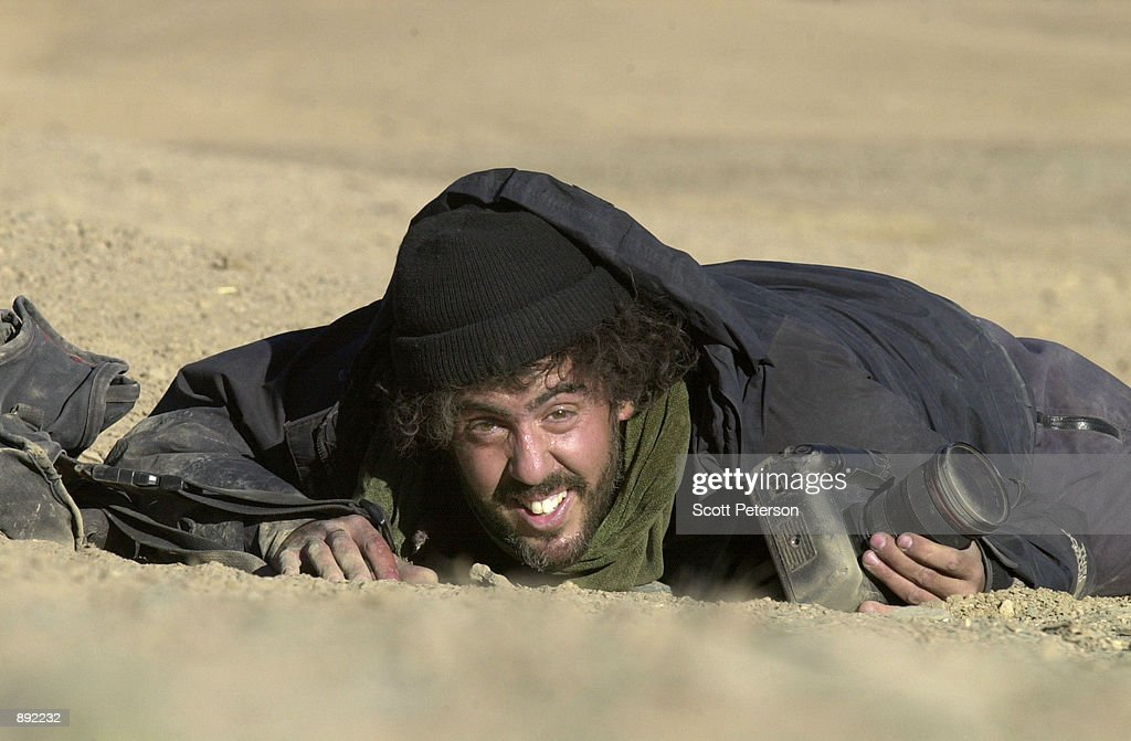Photojournalist Ron Haviv of the VII agency reacts to sniper fire from the Northern Alliance during the surrender of the villages of Midan Shar by...