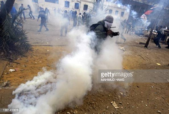 A photojournalist runs for cover from tear gas fired by Egyptian security forces during clashes with protesters near the interior ministry in...
