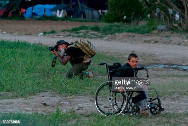 TOPSHOT A photojournalist takes photographs as a refugee boy sits in a wheelchair at the makeshift camp for migrants and refugees at the...