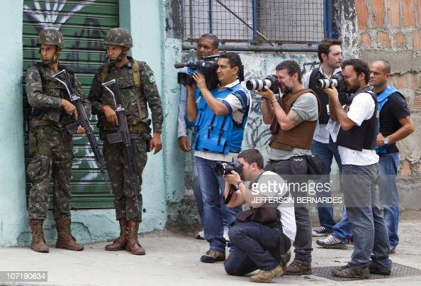 Photojournalists and a cameraman work as Brazilian Army soldiers guard the entrance to the Morro de Alemao shantytown on November 27 2010 in Rio de...
