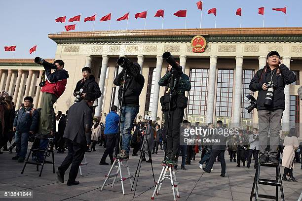 Photojournalists standing on stools in front of the Great Hall of the People during the opening session of the China's National People's Congress on...