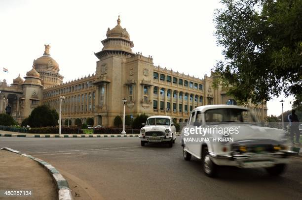 Government owned Ambassador cars of bureaucrats exit the state legislative assembly building the 'Vidhana Soudha' in Bangalore on June 2 2014 The...