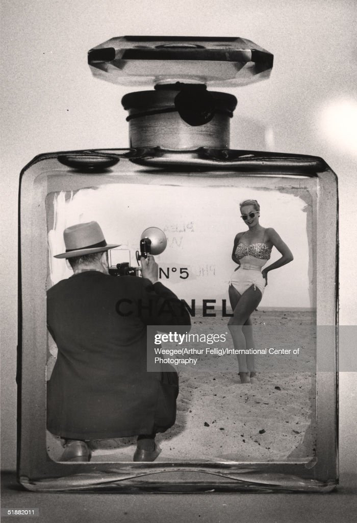 Photomontage of American photographer Weegee (1899 - 1968) taking a photograph of a woman in a bathing suit inside a Chanel No. 5 cologne bottle, late 1950s. (Photo by Weegee(Arthur Fellig)/International Center of Photography/Getty Images)