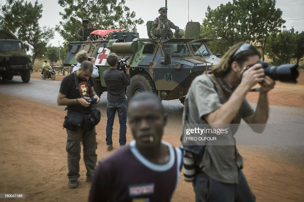 Photoreporters work as French army troopers arrive at the base camp, on January 25, 2013 in Sevare. French and Malian troops advanced on the key Islamist stronghold of Gao after recapturing the northern town of Hombori as the extremists bombed a strategic bridge to thwart a new front planned in the east. The French-led assault against the radical Islamists controlling northern Mali entered its third week with a strong push into the vast semi-arid zone amid rising humanitarian concerns for people in the area facing a dire food crisis.