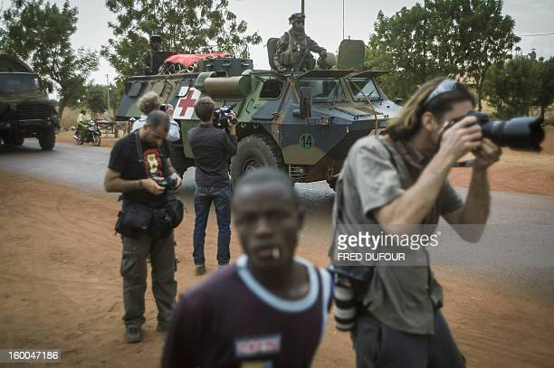 Photoreporters work as French army troopers arrive at the base camp on January 25 2013 in Sevare French and Malian troops advanced on the key...