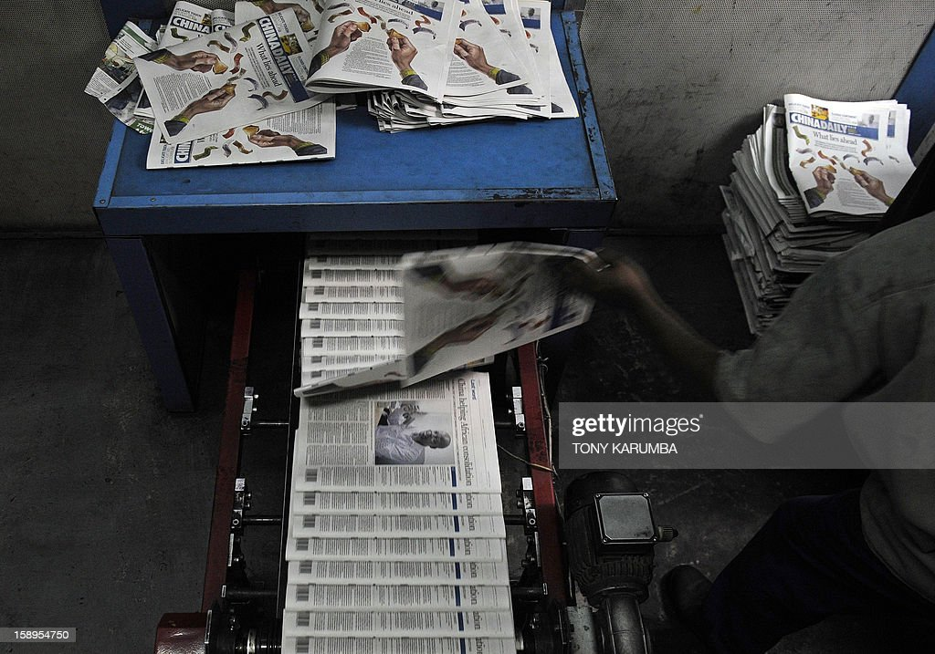 Photos made January 03, 2013 in Nairobi shows a technician pulling a copy of Chinese owned newspaper, China Daily from the line to check for faults at a printing press. Launched in December, the newspaper is Beijing's latest venture on the continent and it aims to look in depth at what the precise nature of Chinese involvement in Africa is, and also at the prominent role many Africans are now playing in China itself, according to publisher and editor-in-chief of the state-run paper Zhu Ling. 'The relationship between China and the African continent is one of the most significant relationships in the world today,' Ling wrote on a commentary in the inaugural copy. AFP PHOTO/ Tony KARUMBA