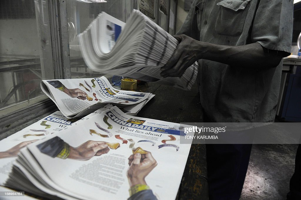 Photos made January 03, 2013 in Nairobi shows a technician stacking copies of Chinese owned newspaper, China Daily fresh at the printing press in the Kenyan capital. Launched in December, the newspaper is Beijing's latest venture on the continent and it aims to look in depth at what the precise nature of Chinese involvement in Africa is, and also at the prominent role many Africans are now playing in China itself, according to publisher and editor-in-chief of the state-run paper Zhu Ling. 'The relationship between China and the African continent is one of the most significant relationships in the world today,' Ling wrote on a commentary in the inaugural copy. AFP PHOTO/ Tony KARUMBA