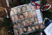 Photos of Sandy Hook Elementary School massacre victims sits at a small memorial near the school on January 14 2013 in Newtown Connecticut The town...
