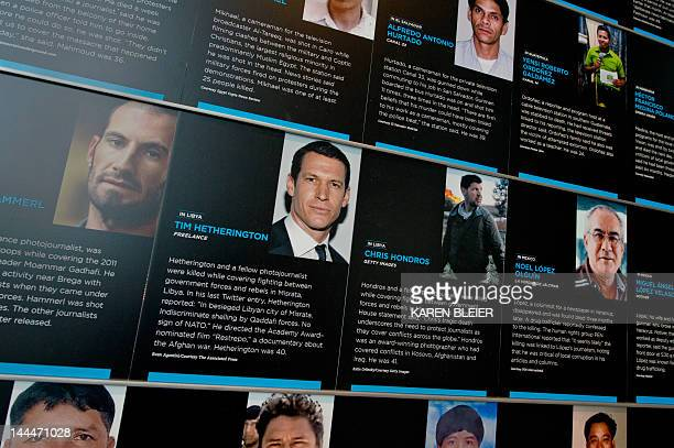 Photos of slain photojournalists Tim Hetherington and Chris Hondros are seen at the journalists memorial wall during a rededication ceremony at the...