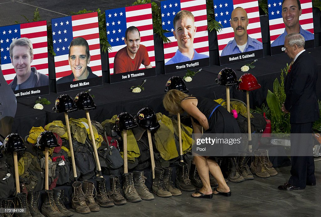 Photos of some of the 19 fallen firefighters line the front of the stage before a memorial service at Tim's Toyota Center July 9, 2013 in Prescott Valley, Arizona. The fire gear is not from the firefighters who died. The firefighters, of the Granite Mountain Hotshots crew, died battling the fast-moving wildfire on June 30.