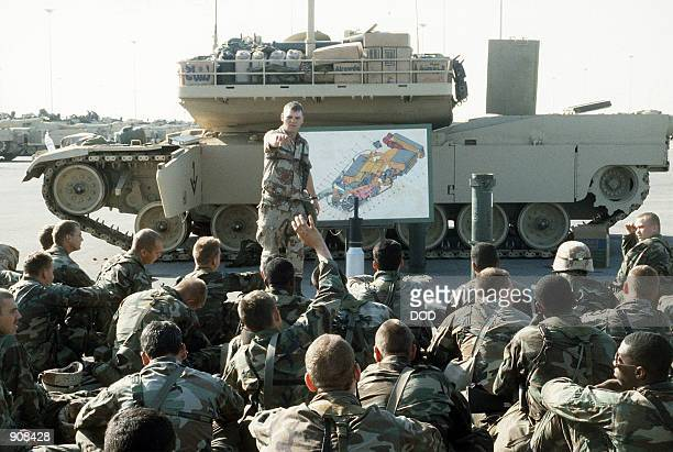 Soldiers receive instruction about the 120mm round to be used in the M1A1 Abrams main battle tank during Operation Desert Shield