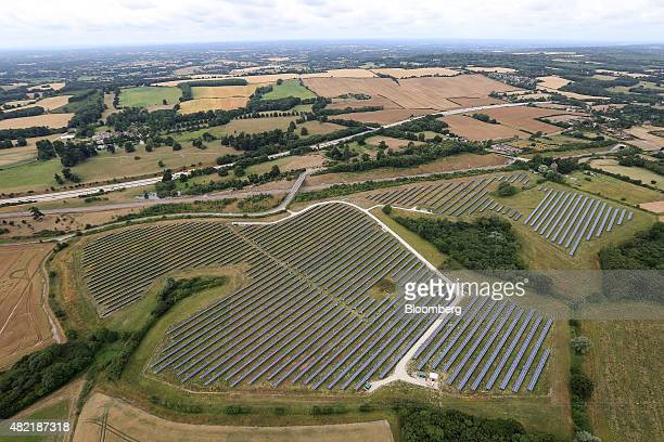 Photovoltaic panels sit on a solar farm in this aerial photograph taken near Ashford UK on Wednesday July 22 2015 The UK proposed to reduce support...