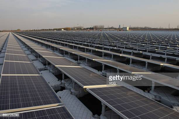 A photovoltaic plant is under construction above a pond at the mining subsidence area in Nihe Town on December 11 2017 in Huainan Anhui Province of...