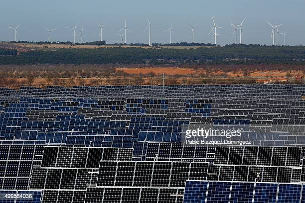 Photovoltaic power panels stand at Abaste's El Bonillo Solar Plant while wind turbines spin at a wind farm on the background on December 2 2015 in El...