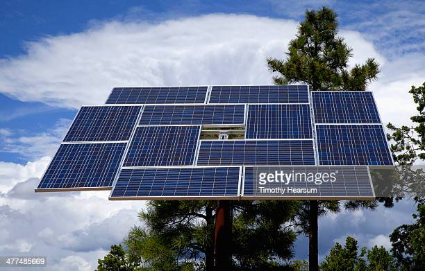 Photovoltaic solar panel with trees and clouds