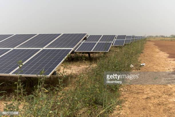 Photovoltaic solar panels sit in an array at the Senergy Santhiou Mekhe PV solar plant in Thies Senegal on Monday Oct 16 2017 The electricity...