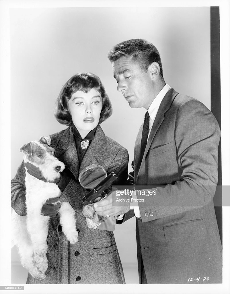 Phyllis kirk holding asta the pup as peter lawford magnifies spot on gun for her