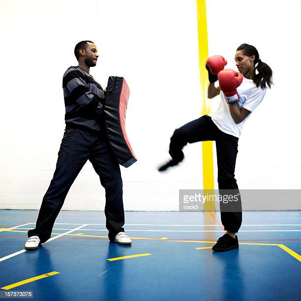 physical education: female kick boxer and trainer in training session