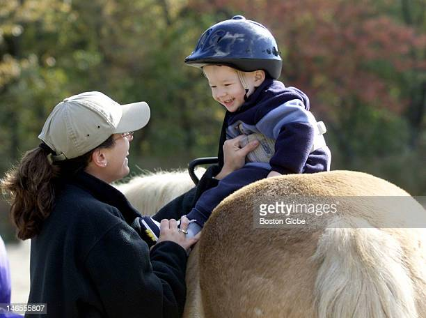 Physical therapist Amy Bolyard works with Connor Sutherland of Winchester as he rides Telleman during a physical therapy program using horses to help...