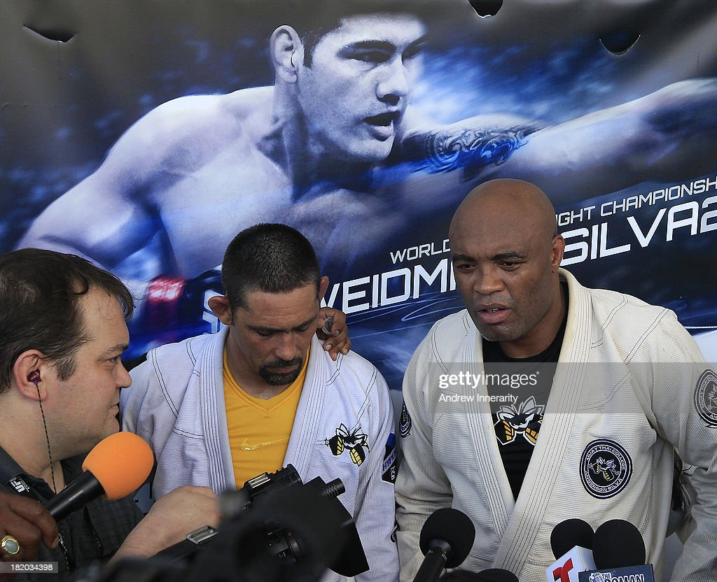 Physical therapist and sparring partner Guto Demaske (C) listens as former UFC middleweight champion Anderson Silva (R) speak to the media during the UFC 168: Weidman v SIlva 2 press tour at Klipsch Amphitheater at Bayfront Park on September 27, 2013 in Miami, Florida.