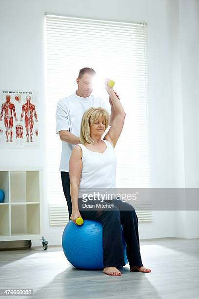 Physical therapist assisting female patient exercising at medica