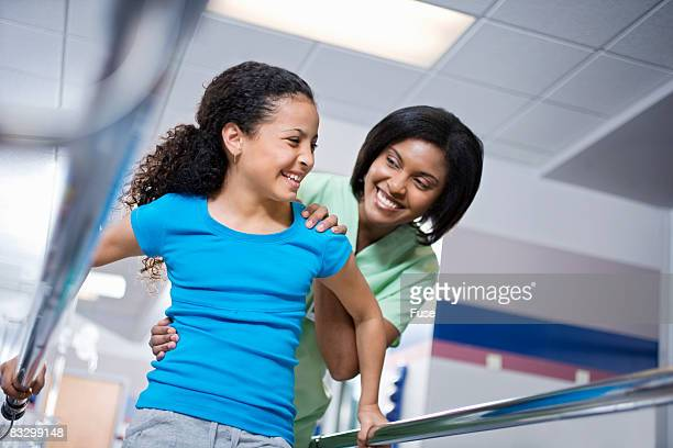 Physical Therapist Assisting Girl
