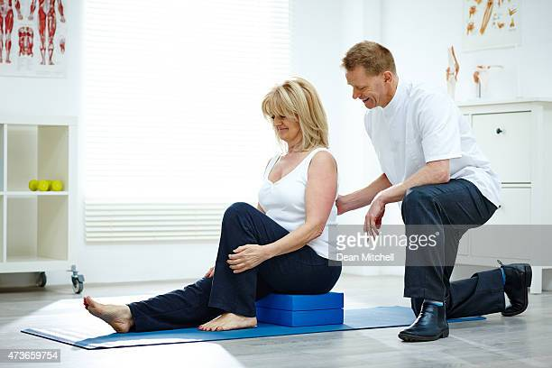 Physical therapist assisting mature woman in gym at hospital