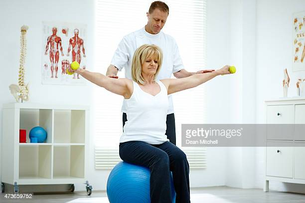 Physical therapist assisting senior woman at medical gym