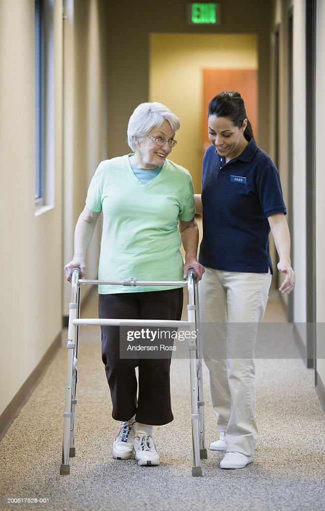 Physical therapist assisting senior woman with walker in corridor : Stock Photo