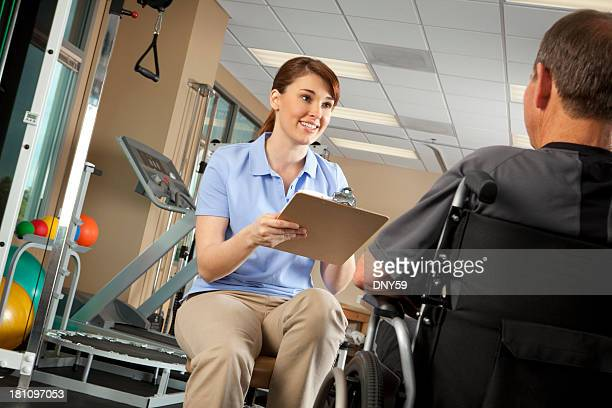 Physical therapist doing an evaluation of patient in a wheelchair
