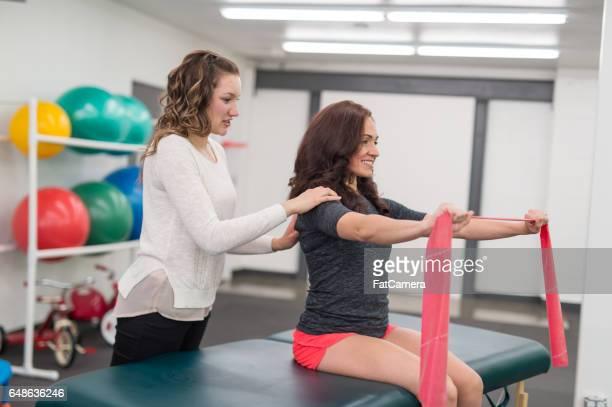 Physikalische Therapeuten tun erstreckt sich mit Patienten